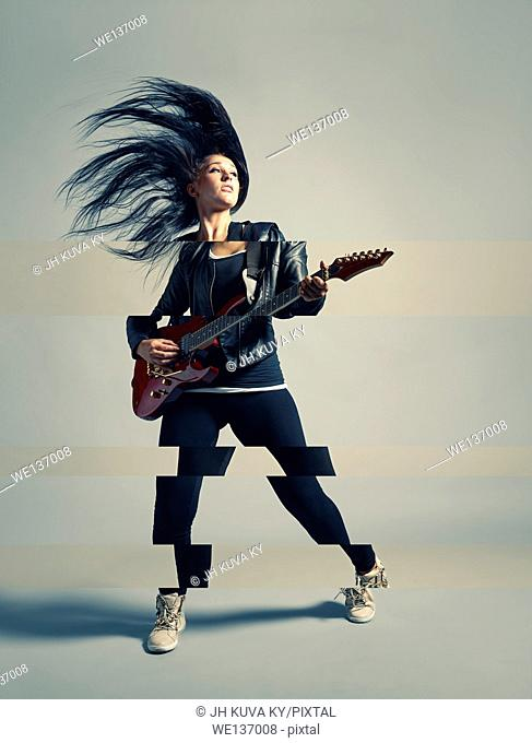 Woman rocker and an electric guitar, studio shot, cross processed image