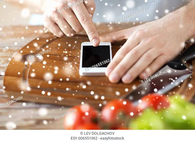 cooking, people, technology and home concept - close up of man reading recipe from smartphone and vegetables on table in kitchen