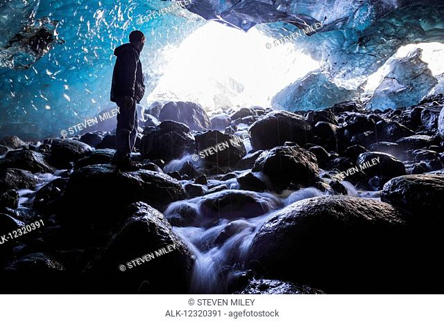 A man stands on a boulder inside an ice cave beneath Root Glacier in Wrangell-St. Elias National Park, Southcentral Alaska, USA