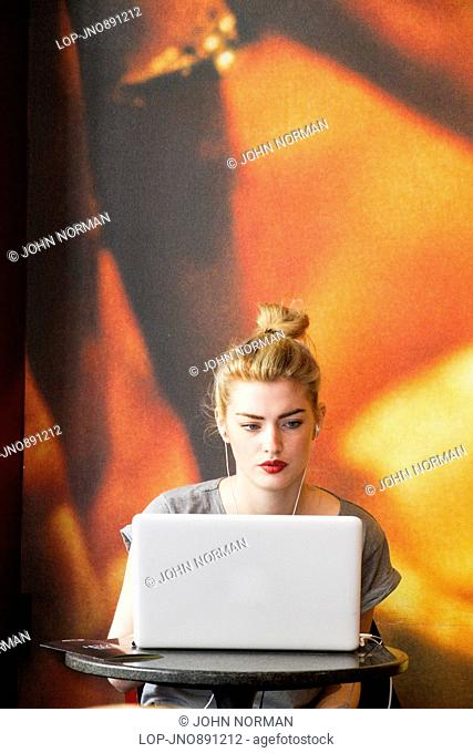 A young woman working at her lap-top in a Soho coffee-shop