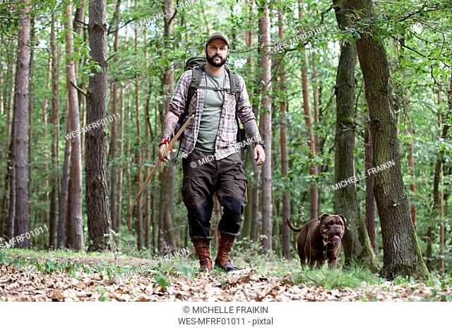 Man with bow and arrow walking with dog in forest