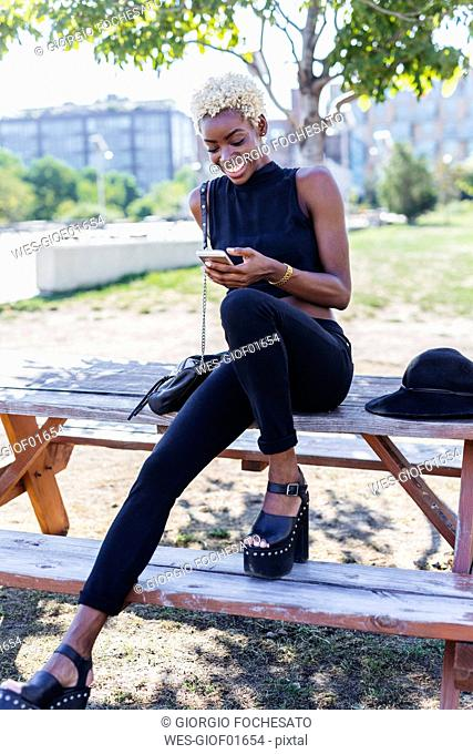 Smiling young woman sitting on wooden table looking on cell phone