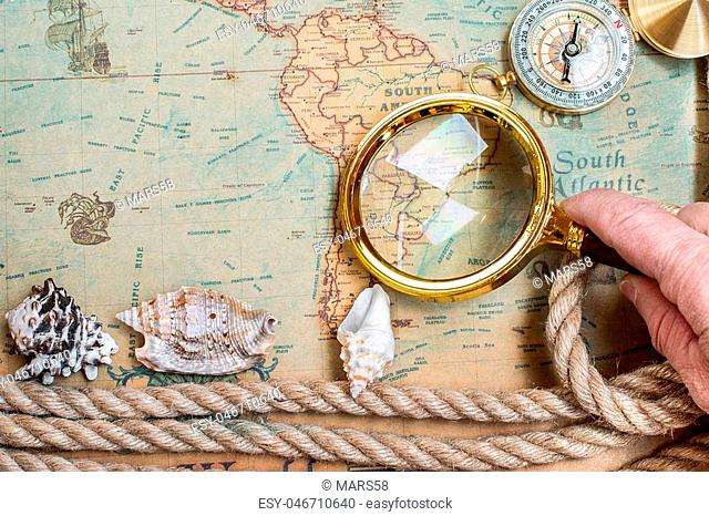 Old vintage retro compass, magnifying glass on ancient world map. Vintage still life. Travel geography navigation concept background