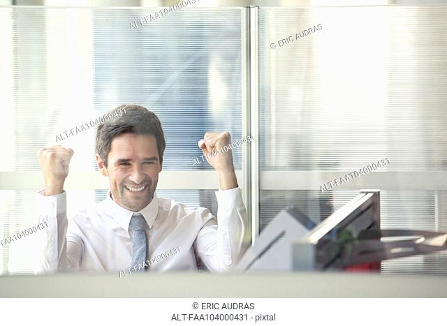Businessman watching sports match on computer at work