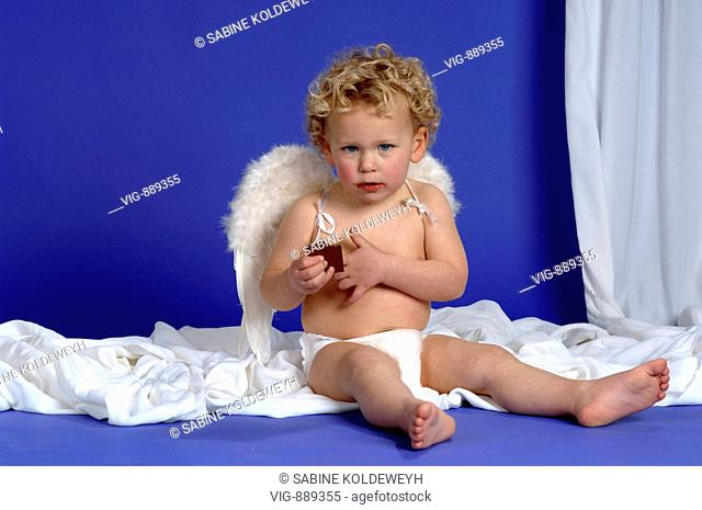 Little boy with angel's wings eating chocolate. - 30/06/2008