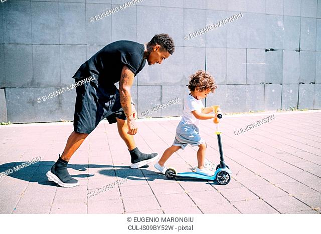 Father teaching son ride push scooter in park