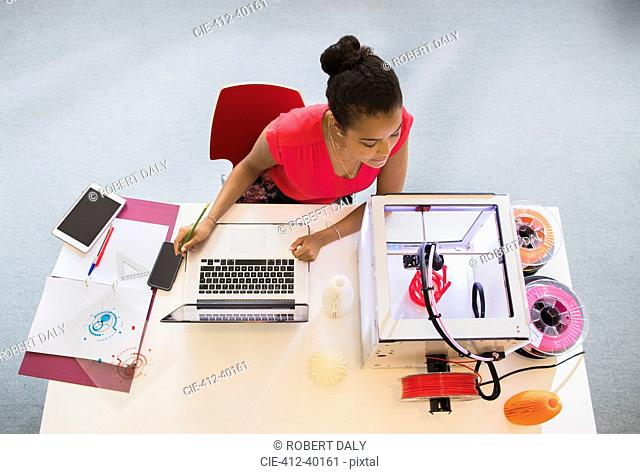Female designer at laptop watching 3D printer