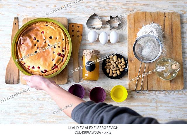 Overhead view of female hand picking up baked cake at kitchen counter
