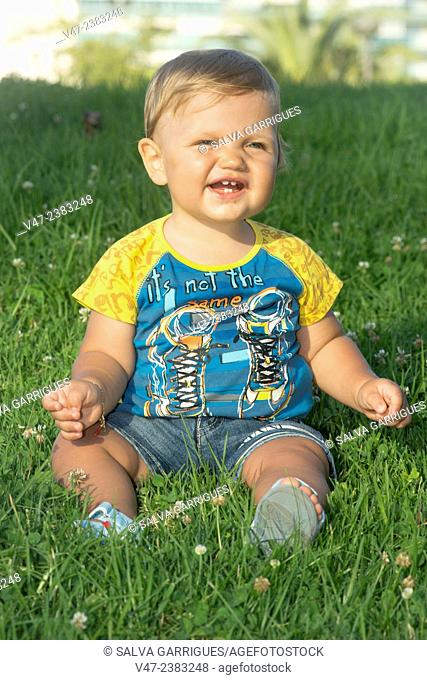 Portrait of a baby sitting on the grass in the garden