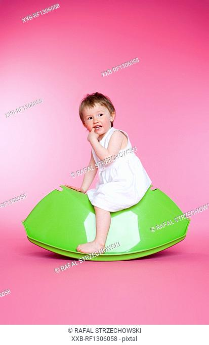 small girl sitting on toy