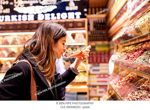 Young woman smelling food in market, Istanbul, Turkey