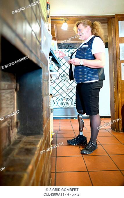 Mid adult woman with prosthetic leg, working cash register at restaurant