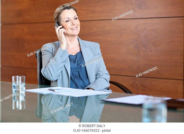 Smiling businesswoman talking on cell phone in conference room
