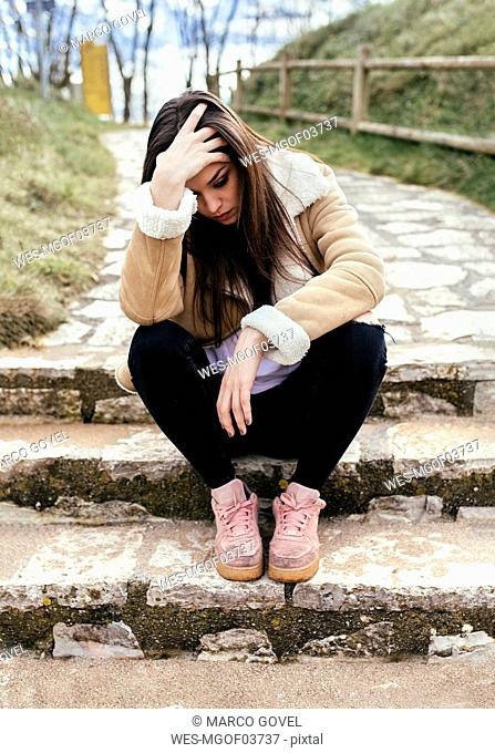 Sad young woman sitting outdoors on steps