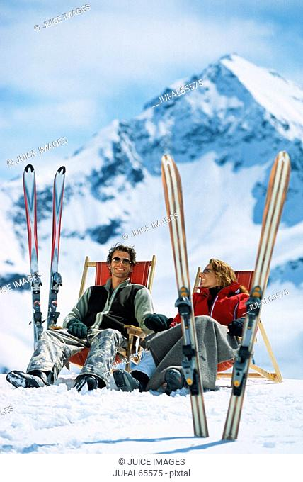 Couple relaxing outdoors with skis