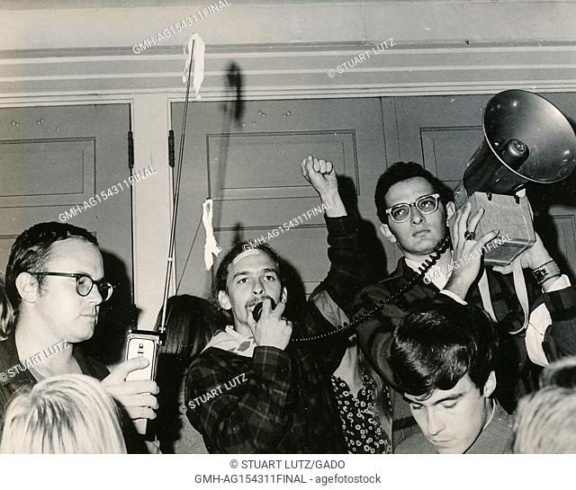 Student wearing hippie attire holding his fist into the air and speaking into the microphone of a bullhorn loudspeaker during an anti Vietnam War student sit-in...