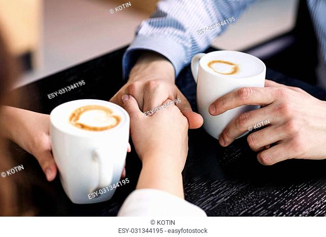 Hands on the table holding cups of coffee