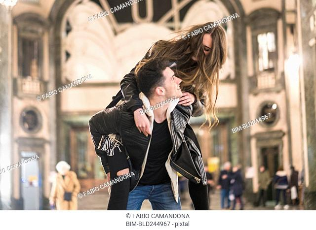 Caucasian man carrying woman piggyback in lobby