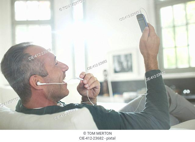 Close up of older man with earbuds talking on cell phone