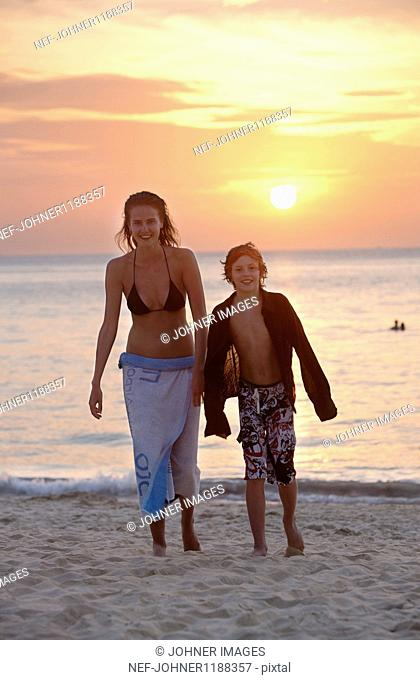 Boy and girl walking on beach at sunset