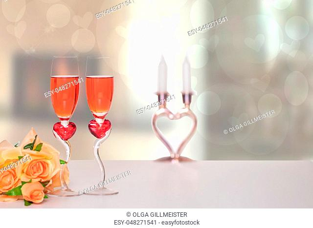 Valentine Day background. A bright table top with two glasses in shape of red hearts with champagner and a bouquet in front of abstract blurred background