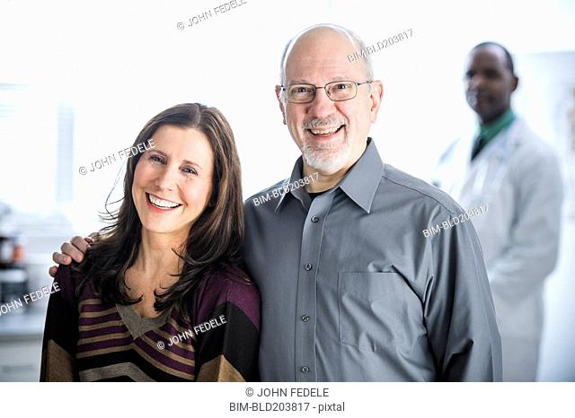 Smiling couple standing in doctor's office