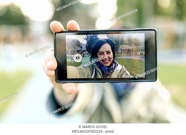Mature woman taking selfie, holding smart phone
