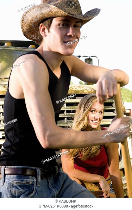 Young woman sitting on truck and young man wearing cowboy hat