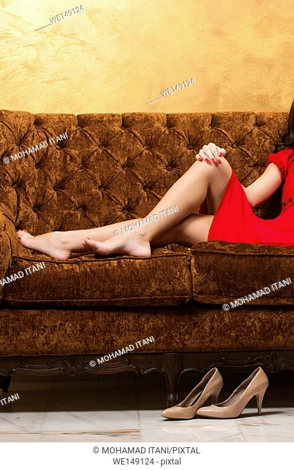 barefooted young woman wearing short red dress sitting on the couch