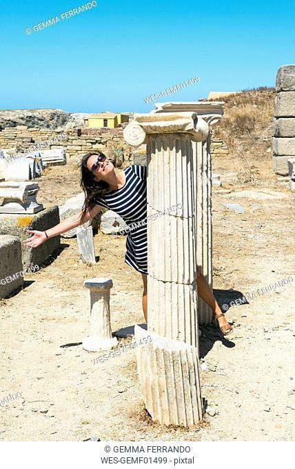 Greece, Mykonos, Delos, happy woman visiting archaeological site