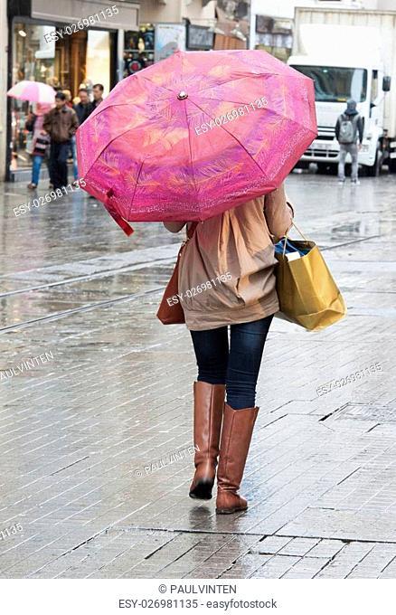 Woman walking in rain down city center high street with umbrella