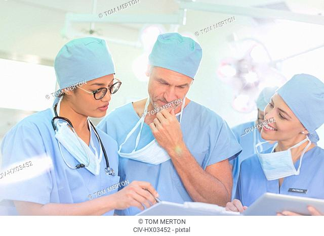 Surgeons reviewing paperwork in operating room