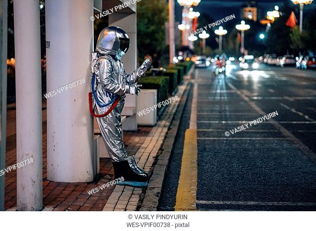 Spaceman standing at a bus stop at night holding cell phone