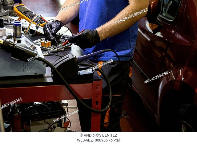 Mechanic fixing an electronic car parts in his workshop