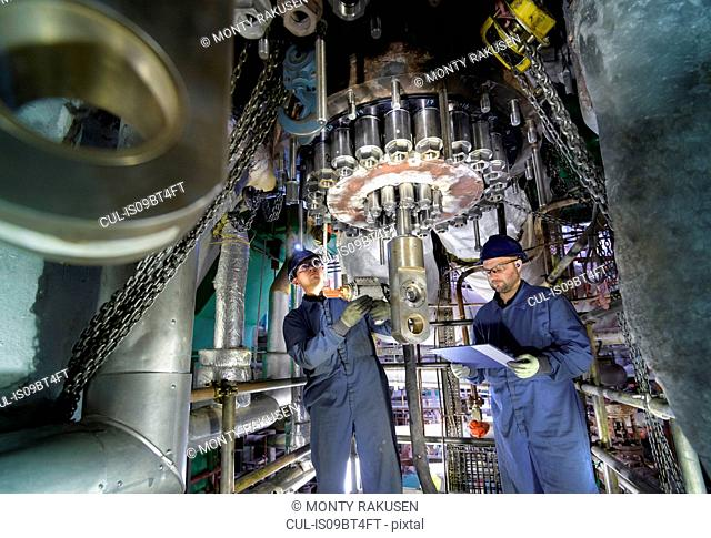 Engineers working in confined space under turbine during outage in nuclear power station