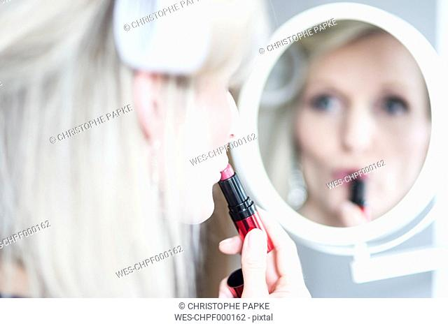 Blond woman with curlers applying lipstick