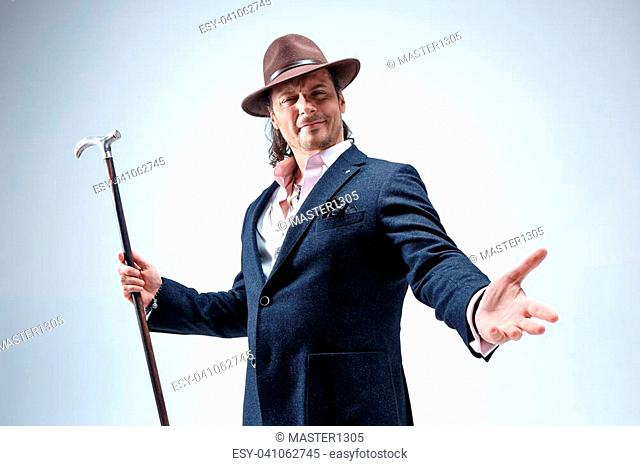 The mature bearded man in a suit and hat holding cane. Isolated on a gray studio background