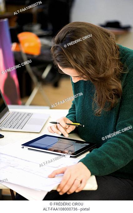 Architect using digital tablet to prepare design