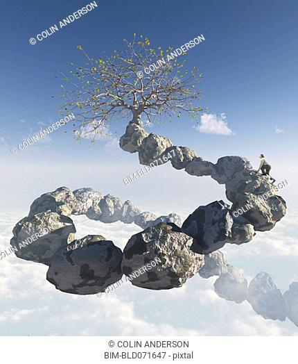 Man climbing rocks in sky towards tree