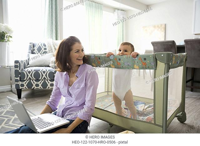 Mother sitting by baby crib with laptop