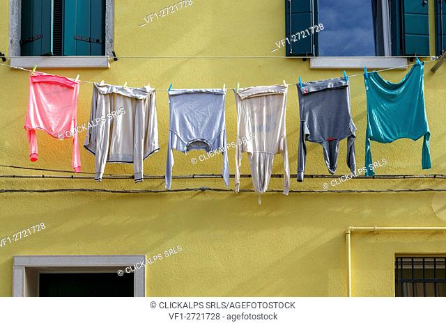 Europe, Italy, Veneto, Chioggia. Hanging clothes on a old house facade