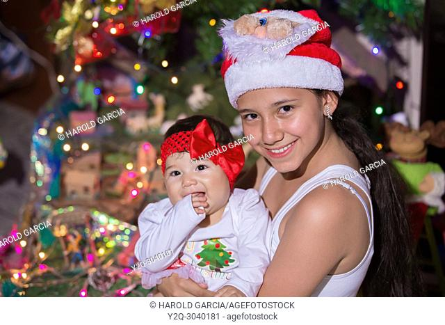 Sisters celebrating Christmas near a tree decorated with lights and Christmas decorations