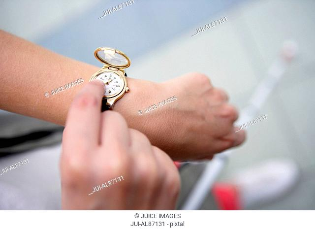 Blind person checking Braille watch