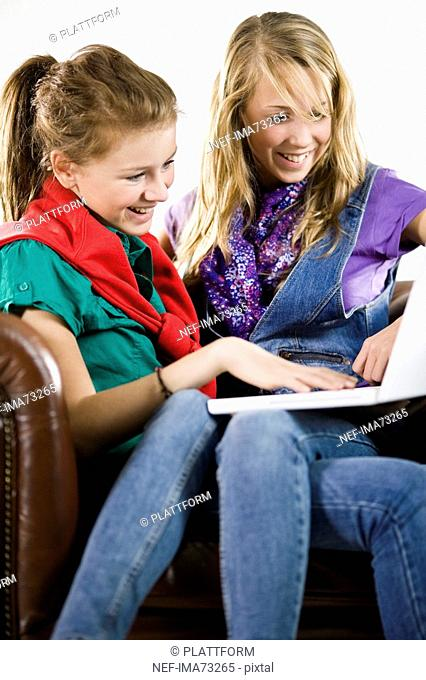 Teenage girls in an armchair using a laptop