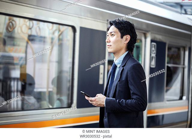 Businessman wearing suit standing at train station platform, holding mobile phone