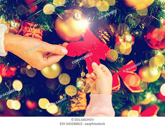 family, holidays, new year and people concept - close up of mother and child hands decorating christmas tree