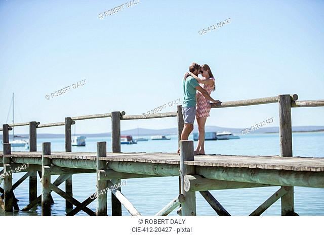 Couple hugging on wooden dock
