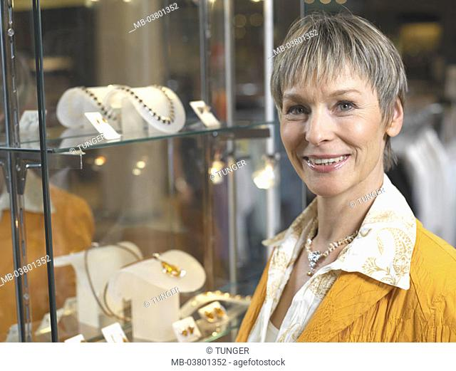 Jeweler business, Glasvitrine,  Pieces of jewelry, woman, middle age,  smiling, portrait Series, women portrait, 40-50 years, well Age, gaze camera