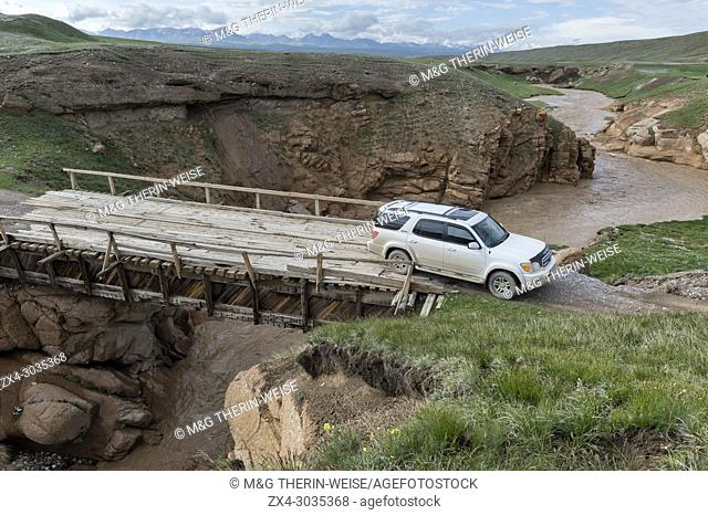 Four wheel drive car crossing a wooden bridge over a wild gorge, Naryn Province, Kyrgyzstan