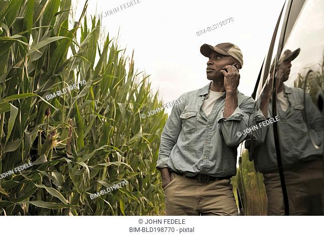 African American farmer talking on cell phone in field